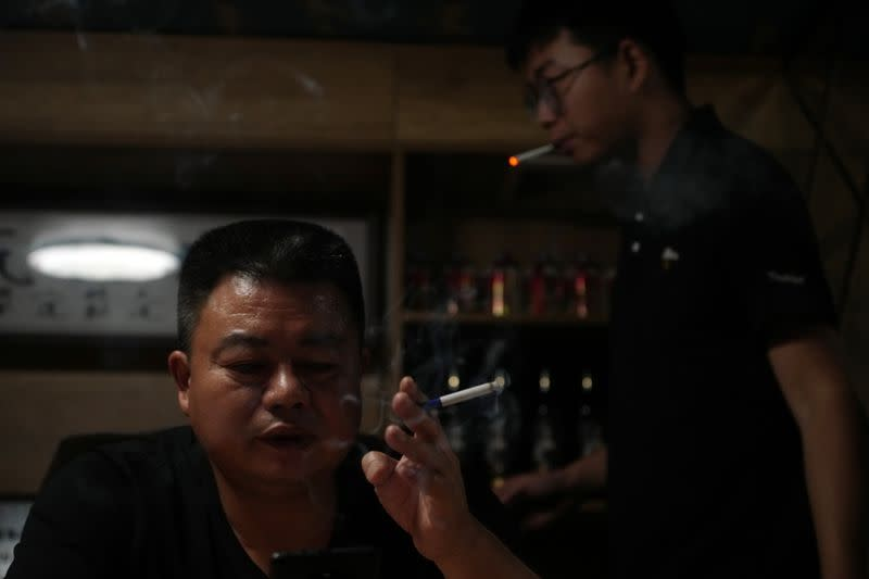 Guo Hui smokes a cigarette at his office in Guangzhou