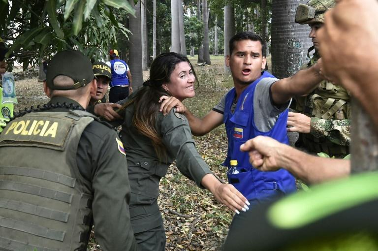 A member of Venezuela's military (C) is escorted into Colombia, having deserted