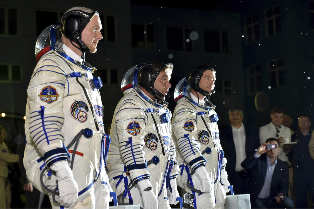 European Space Agency's astronaut Alexander Gerst, left, Russian cosmonaut Maxim Suraev, center, and NASA astronaut Reid Wiseman, crew members of the mission to the International Space Station, ISS, report to members of the State Committee prior the launch of Soyuz-FG rocket at the Russian leased Baikonur cosmodrome, Kazakhstan, Wednesday, May 28, 2014. (AP Photo/Kiril Kudryavtsev, Pool)