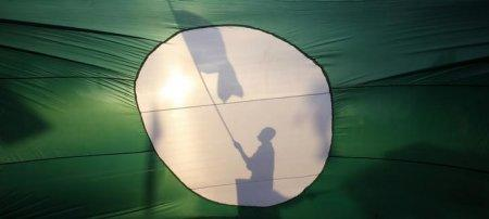 A supporter of opposition Parti Islam se-Malaysia (PAS) is silhouetted on its giant flag as he campaigns on a street in Pekan, 300 km (186 miles) east of Kuala Lumpur on the eve of the general elections May 4, 2013. Malaysia's opposition enjoys a very narrow lead over the long ruling National Front for the first time in a key poll issued on Friday, two days before an election in the Southeast Asian country. REUTERS/Bazuki Muhammad (MALAYSIA - Tags: POLITICS ELECTIONS TPX IMAGES OF THE DAY)