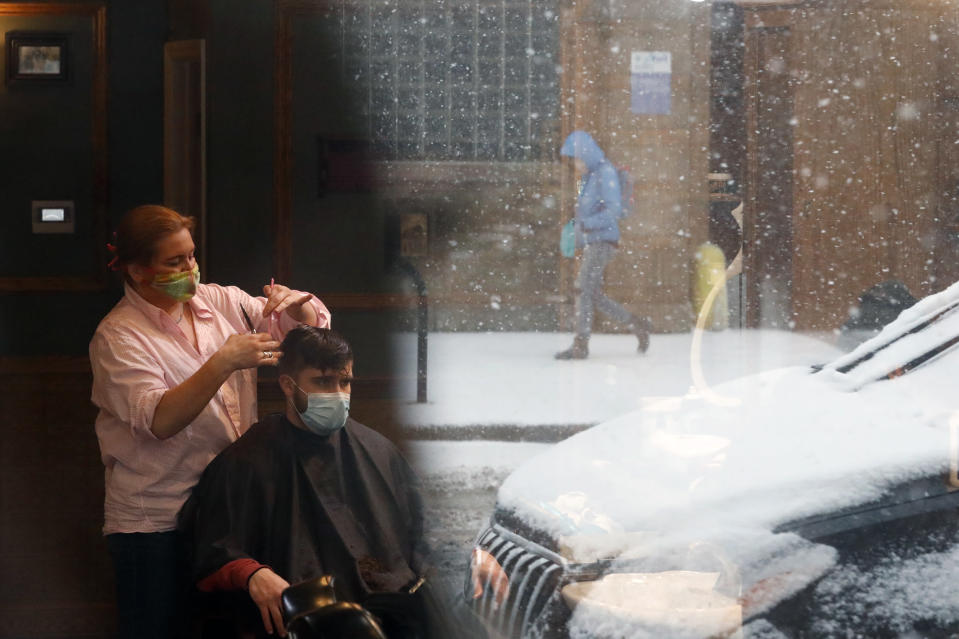Gina Loukas, left, gives a haircut to a customer with a lone pedestrian reflected in the barbershop window Monday, March 15, 2021, as fresh snow falls in Chicago. (AP Photo/Shafkat Anowar)