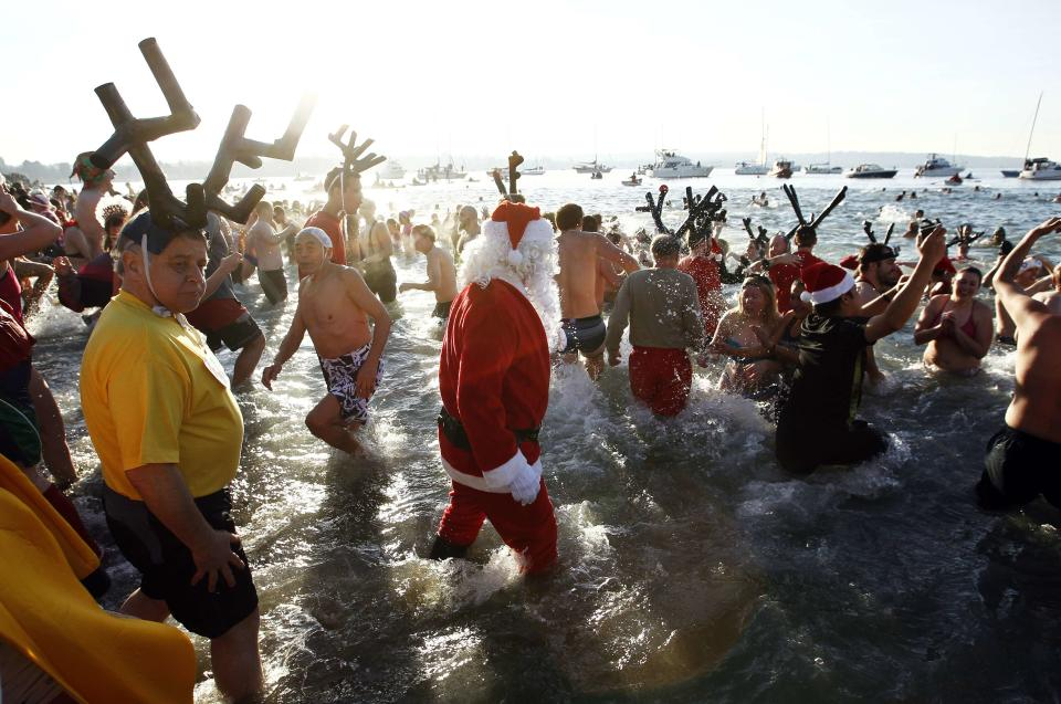 Participants run into English Bay during the 95th annual New Year's Day Polar Bear Swim in Vancouver, British Columbia January 1, 2015. REUTERS/Ben Nelms (CANADA - Tags: ENVIRONMENT SOCIETY ANNIVERSARY)