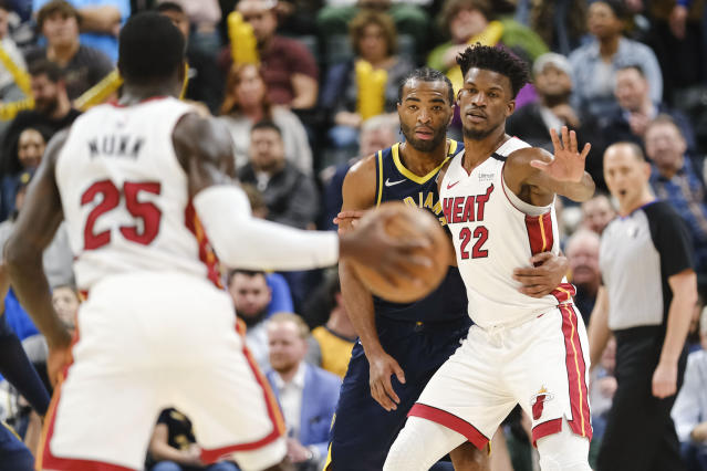 Indiana Pacers forward T.J. Warren, center, defends Miami Heat forward Jimmy Butler (22) during the second half of an NBA basketball game in Indianapolis, Wednesday, Jan. 8, 2020. Warren was called for his second technical foul latter in the play. The Heat won 122-108. (AP Photo/AJ Mast)