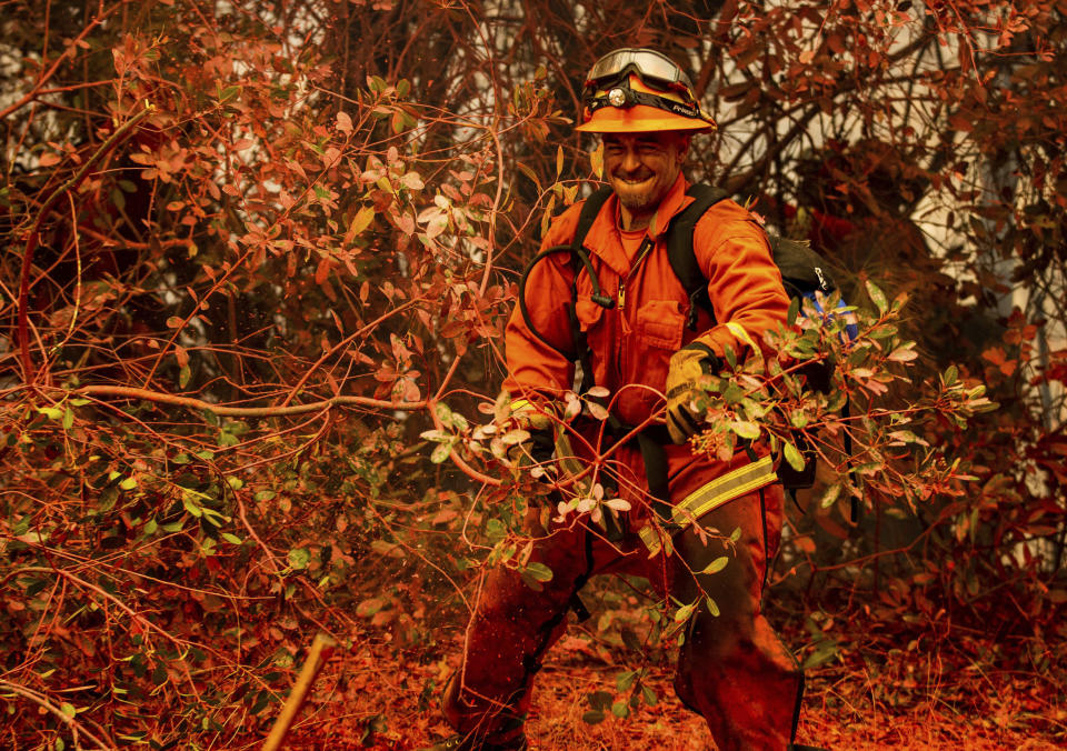 An inmate firefighter clears brush while battling the Fawn Fire burning north of Redding in Shasta County, Calif., on Thursday, Sept. 23, 2021. (AP Photo/Ethan Swope)