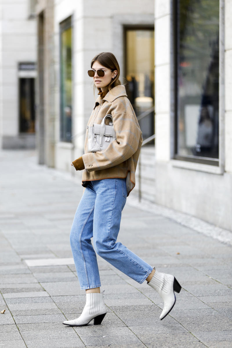 BERLIN, GERMANY - SEPTEMBER 06: Influencer Jacqueline Zelwis wearing a brown turtleneck sweater by Samsoe Samsoe, a light brown Jacket with light grey stripes and a blue Jenas by Baum & Pferdegarten, white cowboy boots by Toral, sunglasses by Prive Revaux and a light grey bag by Philip Lim during a street style shooting on September 6, 2020 in Berlin, Germany. (Photo by Streetstyleshooters/Getty Images)