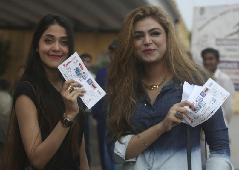 Pakistani cricket fans show their tickets at the National stadium in Karachi, Pakistan, Friday, Sept. 27, 219. Heavy rain has delayed the start of the first one-day international between Pakistan and Sri Lanka. An unusual spell of rain in the southern port city of Karachi during this time of the year left the cricket ground completely waterlogged on Friday. (AP Photo/Fareed Khan)