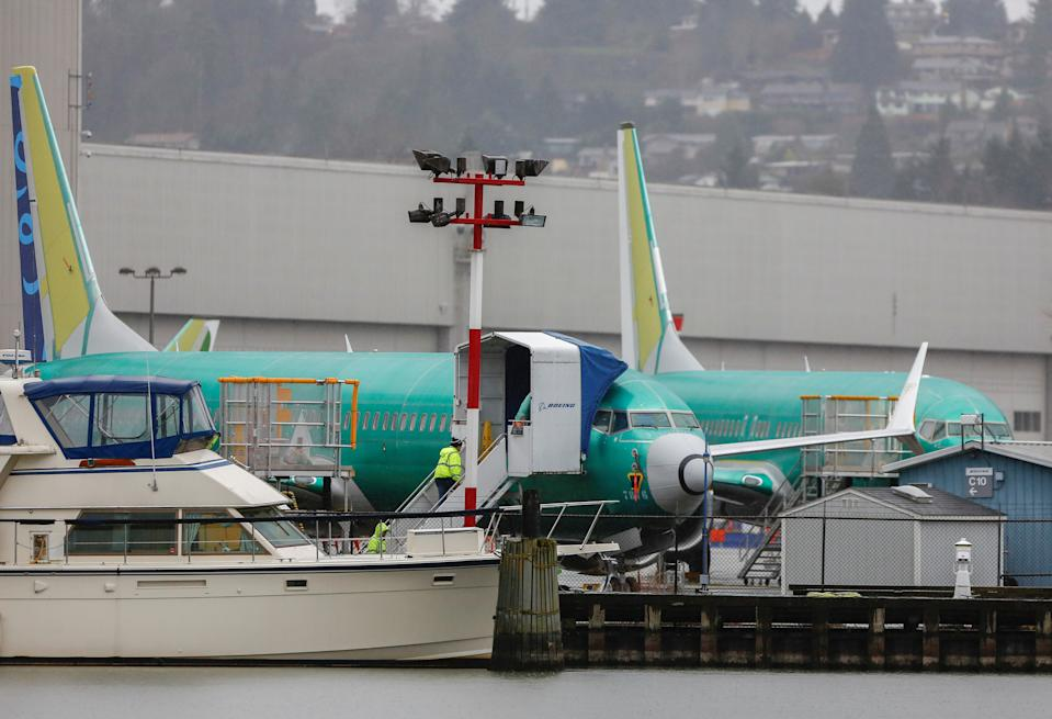 Employees walk up a staircase to a Boeing 737 Max aircraft seen parked outside the company's production facility in Renton, Washington, U.S. January 10, 2020. REUTERS/Lindsey Wasson