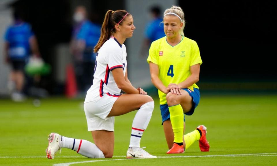 USA's Alex Morgan and Sweden's Hanna Glas take the knee before their football match at Tokyo Stadium.