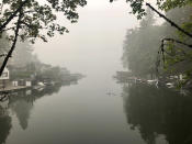 A family of ducks swims on Oswego Lake, which is almost completely obscured by wildfire smoke, in Lake Oswego, Ore. on Monday, Sept. 14, 2020. The entire Portland metropolitan region remains under a thick blanket of smog from wildfires that are burning around the state and residents are being advised to remain indoors due to hazardous air quality. (AP Photo/Gillian Flaccus)