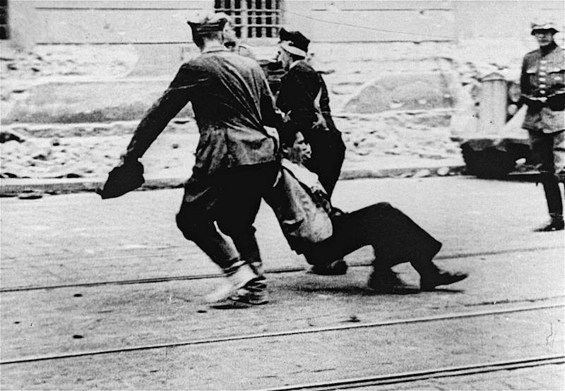 "In this July 1941 photo provided by the United States Holocaust Memorial Museum courtesy of Bernhard Press, civilians drag a Jewish man through a street in Riga, Latvia as a member of the German police looks on. Despite all the Holocaust writings, more news is emerging about 1,000 Nazi-run ghettos that left millions of Jews dead. ""Encyclopedia of Camps and Ghettos, 1933-1945, Volume II"" is a global effort that documents every site of organized Nazi atrocities. (AP Photo/United States Holocaust Memorial Museum) MANDATORY CREDIT: UNITED STATES HOLOCAUST MEMORIAL MUSEUM. ONE TIME USE ONLY, NO ARCHIVING"