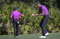 Tiger Woods, right, reacts after his son Charlie sank a putt on the third green during the first round of the PNC Championship golf tournament, Saturday, Dec. 19, 2020, in Orlando, Fla. (AP Photo/Phelan M. Ebenhack)