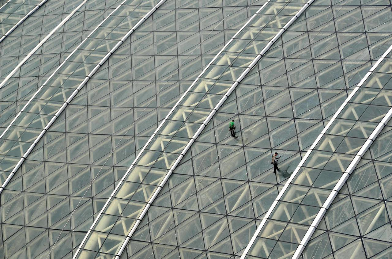 "Workers clean the glass roof of the ""New Century Global Centre"" building, which opened to the public in Chengdu, southwest China's Sichuan province on June 28, 2013.  The center, claimed by Chinese officials to be ""the world's largest standalone structure"", measuring 500 metres in length and 400 metres in width, with 1.7 million square metres of floor space -- big enough to hold 20 Sydney Opera Houses -- is the latest symbol of China's economic boom.       CHINA OUT           AFP PHOTO"