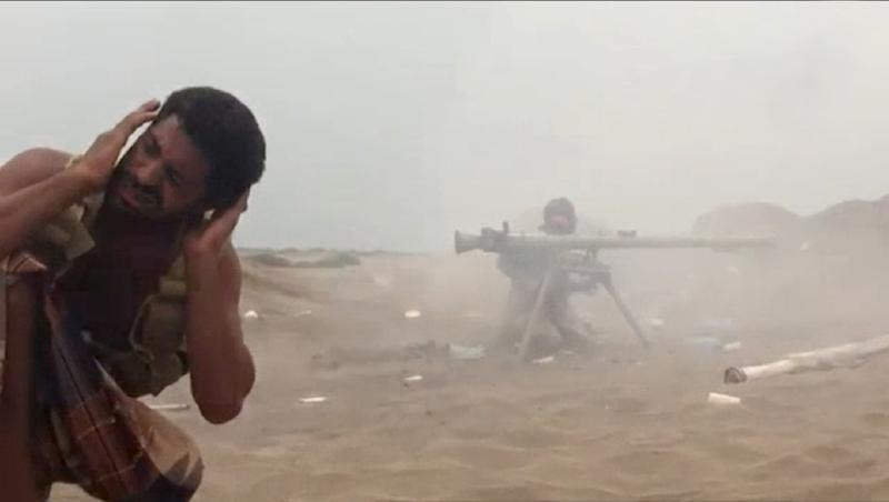An image grab from AFPTV video shows a pro-government Yemen fighter bracing as another fires a recoilless gun in Yemen's Hodeida province on June 16, 2018 (AFP Photo/-)