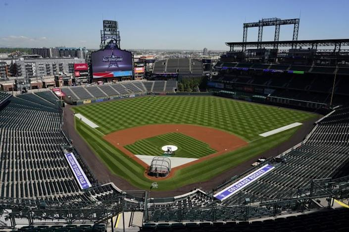 A handful of players warm up before a baseball game in Coors Field as the Colorado Rockies host the Texas Rangers Thursday, June 3, 2021, in Denver. (AP Photo/David Zalubowski)