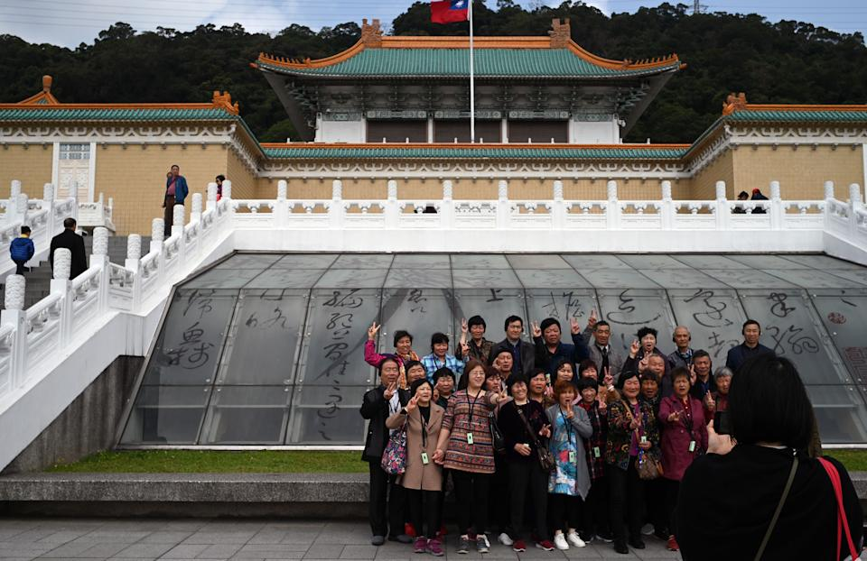 Tourists pose for photos in front of Taiwan's National Palace Museum in Taipei on March 13, 2019. (Photo by Sam YEH / AFP)        (Photo credit should read SAM YEH/AFP/Getty Images)