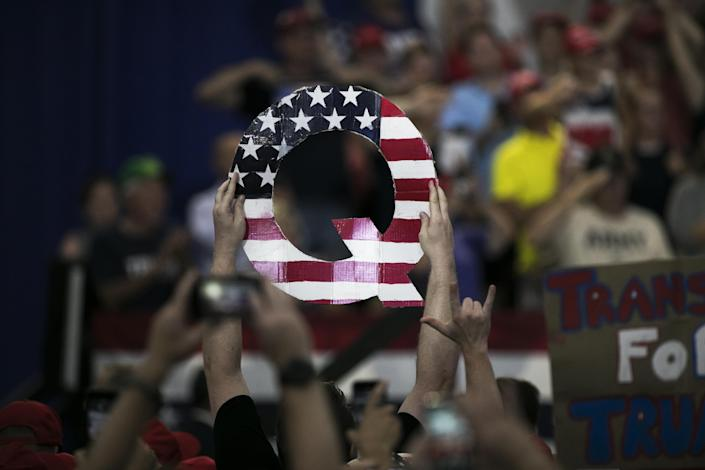"""An attendee holds signs a sign of the letter """"Q"""" before the start of a rally with U.S. President Donald Trump in Lewis Center, Ohio, U.S., on Saturday, Aug. 4, 2018. (Maddie McGarvey/Bloomberg via Getty Images)"""