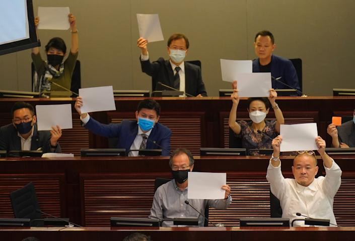 """Pro-democracy lawmakers raise white papers to protest during a meeting to discuss the new national security law at the Legislative Council in Hong Kong. <span class=""""copyright"""">(Vincent Yu / Associated Press)</span>"""
