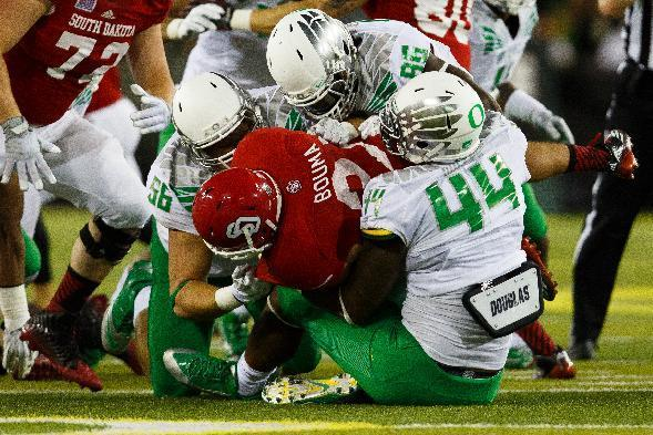 The Oregon defense stops South Dakota running back Trevor Bouma (21) during the first quarter of an NCAA college football game in Eugene, Ore., Saturday, Aug. 30, 2014. (AP Photo/Ryan Kang)