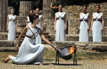 Greek actress Katerina Lehou , playing the role of High Priestess, lights a torch from the sun's rays reflected in a parabolic mirror during the dress rehearsal for the Olympic flame lighting ceremony for the Rio 2016 Olympic Games at the site of ancient Olympia in Greece. REUTERS/Yannis Behrakis