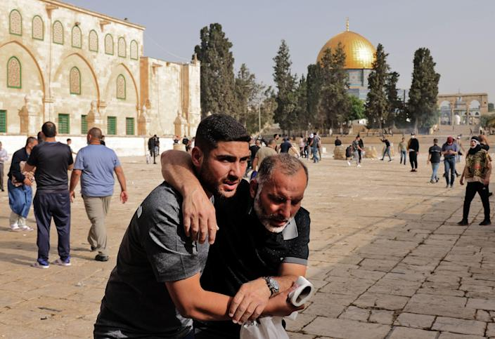 A Palestinian man helps a wounded fellow protester amid clashes with Israeli security forces at Jerusalem's Al-Aqsa mosque compound on May 10, 2021, ahead of a planned march to commemorate Israel's takeover of Jerusalem in the 1967 Six-Day War.