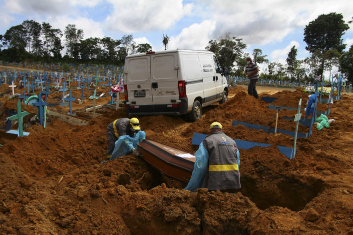 FILE - In this Jan. 6, 2021 file photo, cemetery workers bury 89-year-old Abilio Ribeiro, who died of the new coronavirus, at the Nossa Senhora Aparecida cemetery in Manaus, Amazonas state, Brazil. The country has suffered more than 200,000 COVID-19 deaths, the second-highest total in the world after the United States, with infections and deaths surging again. (AP Photo/Edmar Barros)