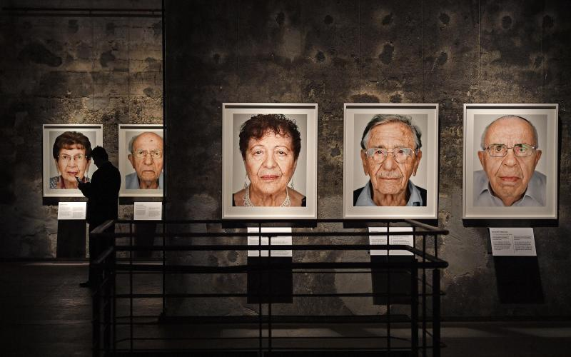 A man walks beside photos of the exhibition 'Survivors - Faces of Life after the Holocaust' at the former coal mine Zollverein in Essen, Germany, Tuesday, Jan. 21, 2020. The world heritage landmark Zollverein shows 75 years after the liberation of the Nazi death camp Auschwitz-Birkenau, 75 portraits of Jewish survivors, photographed in Israel by German artist Martin Schoeller. (AP Photo/Martin Meissner)