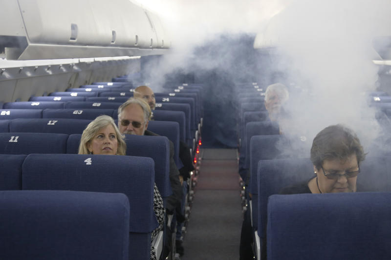 FAA employees participate in a demonstration of an airline cabin filling with smoke, in a simulator at the FAA Civil Aerospace Medical Institute in the Mike Monroney Aeronautical Center, Thursday, Oct. 17, 2019, in Oklahoma City. Federal researchers, using 720 volunteers in Oklahoma City, will test whether smaller seats and crowded rows slow down airline emergency evacuations. (AP Photo/Sue Ogrocki)
