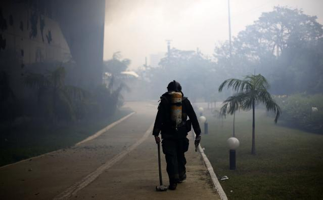A firefighter walks at the scene of a fire at the Latin America Memorial in Sao Paulo November 29, 2013. A large fire sent smoke billowing out of Sao Paulo's Latin America Memorial, designed by celebrated Brazilian architect Oscar Niemeyer, as emergency crews moved into the area to control the flames and rescue people at the scene. It was not clear how the fire started, but local reports indicated it was in the auditorium in the cultural centre where employees were gathered at the time. There were no reports of fatalities by early afternoon, but local TV carried images of people being treated by EMS crews just outside the massive complex as dark smoke continued to rise from the building. REUTERS/Nacho Doce (BRAZIL - Tags: DISASTER)