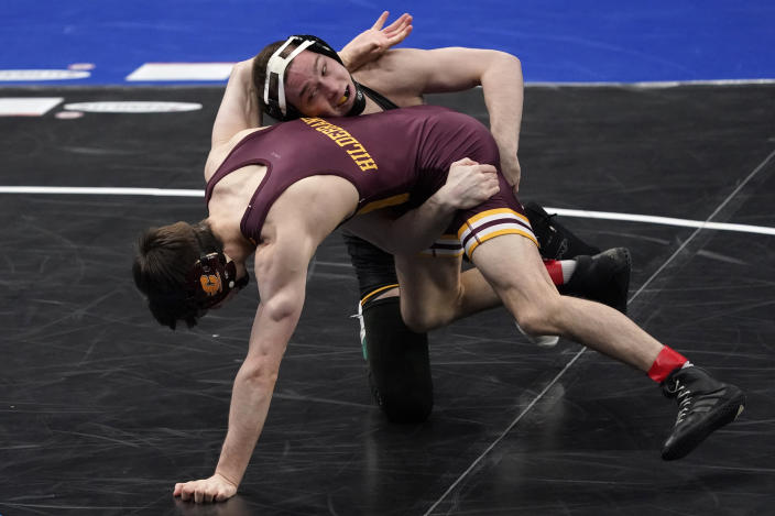Iowa's Spencer Lee, top, takes on Central Michigan's Drew Hildebrandt during their 125-pound match in the semifinal round of the NCAA wrestling championships Friday, March 19, 2021, in St. Louis. (AP Photo/Jeff Roberson)