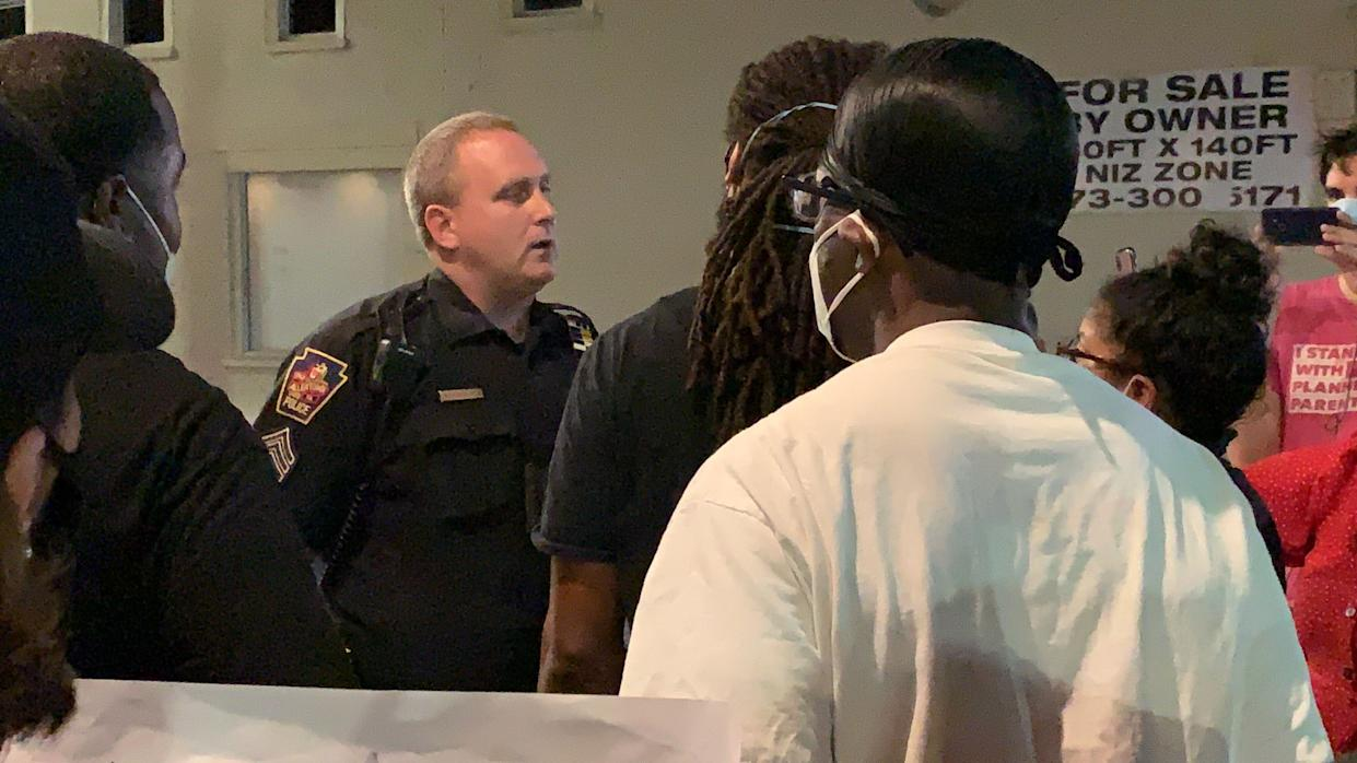 Protesters confront an Allentown police officer outside the 10th Street precinct Saturday night, demanding answers in response to a video that shows an officer pressing his knee into a man's neck.