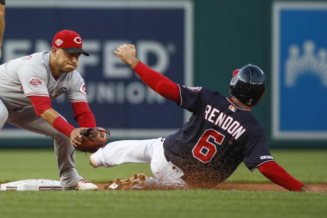 Cincinnati Reds shortstop Jose Iglesias reaches to tag Washington Nationals' Anthony Rendon to complete the double play on a ball hit to first by Juan Soto during the first inning of a baseball game at Nationals Park, Tuesday, Aug. 13, 2019, in Washington. A run scored. (AP Photo/Alex Brandon)