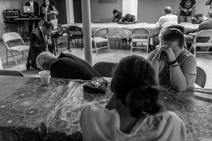 <p>Neighborhood residents attend a free Sunday breakfast and church service at La Requena Belen church in Middletown, Ohio. When the pastor asks if they would like to bow their heads and pray, they do. (Photograph by Mary F. Calvert for Yahoo News) </p>