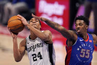 Detroit Pistons guard Delon Wright (55) reaches in on San Antonio Spurs guard Devin Vassell (24) during the second half of an NBA basketball game, Monday, March 15, 2021, in Detroit. (AP Photo/Carlos Osorio)