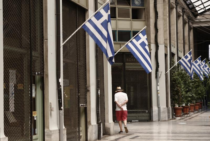 A man walks by a row of closed shops at an arcade in central Athens