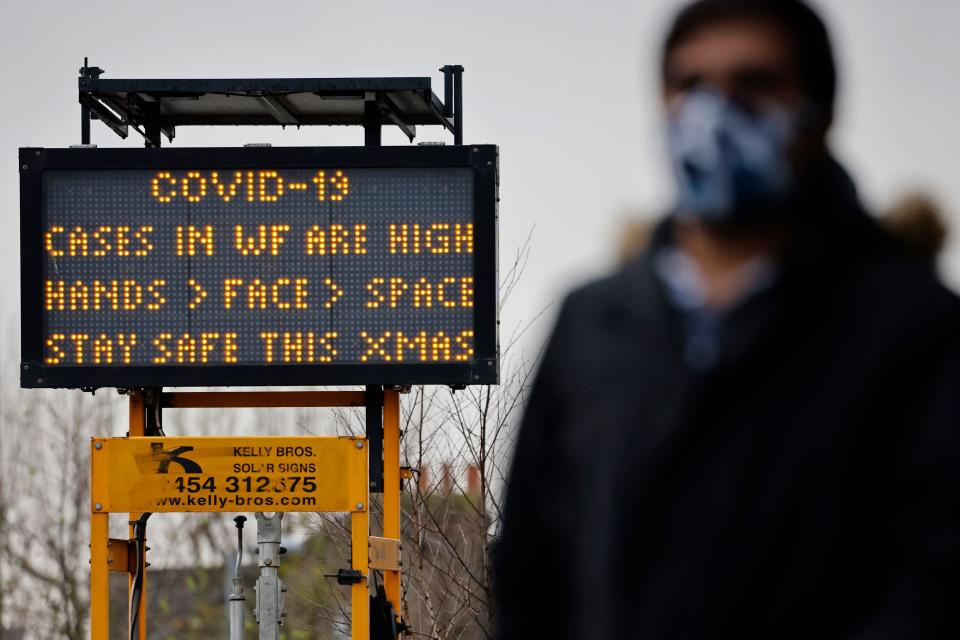 "A pedestrian some wearing a face mask or covering due to the COVID-19 pandemic, walks past Coronavirus information signs in Walthamstow in north east London on December 23, 2020. - Britain's public health service urged Prime Minister Boris Johnson on Wednesday to extend the country's Brexit transition period or risk pushing hospitals already struggling with coronavirus ""over the edge"" in the event of a no-deal departure from the EU single market. (Photo by Tolga Akmen / AFP) (Photo by TOLGA AKMEN/AFP via Getty Images)"