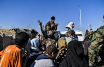A Syrian woman flashes the victory sign as civilians gather on the western front of Raqa after fleeing Islamic State group-held parts of the city fighting on October 12, 2017