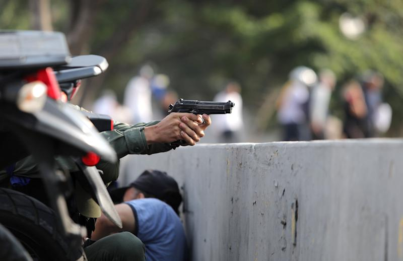 "A military member aims a gun near the Generalisimo Francisco de Miranda Airbase ""La Carlota"", in Caracas, Venezuela April 30, 2019. (Photo: Manaure Quintero/Reuters)"