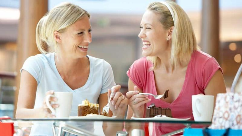Female friends enjoying their dessert together at a mall