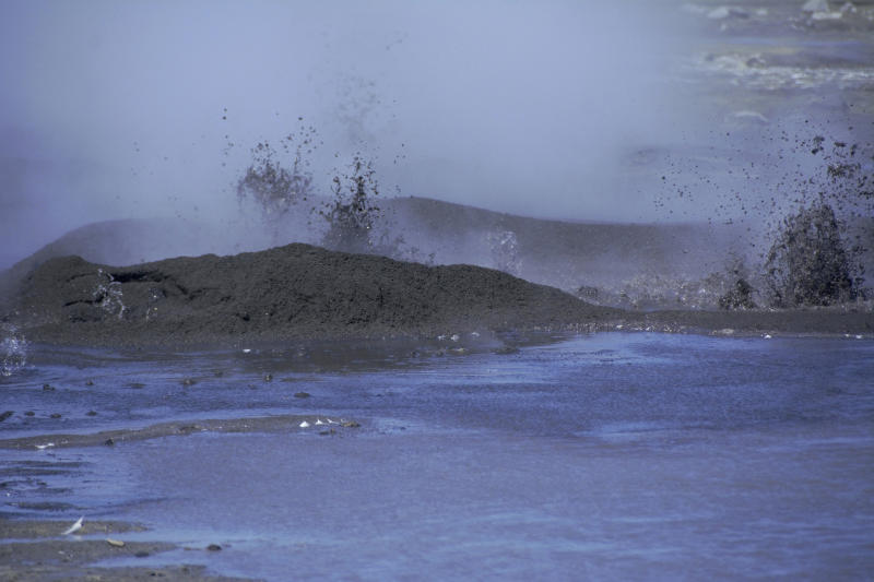 This August 2019 photo released by the National Oceanic and Atmospheric Administration Fisheries (NOAA) shows mud shooting upward from the openings near a volcano on Bogoslof Island, Alaska. Alaska's northern fur seals are thriving on an island that's the tip of an active undersea volcano. Numbers of fur seals continue to grow on tiny Bogoslof Island despite hot mud, steam and sulfurous gases spitting from vents on the volcano. (Maggie Mooney-Seus/NOAA Fisheries via AP)