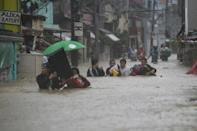 Typhoon Vamco brought heavy flooding to suburban Manila on Thursday, with authorities warning of life-threatening storm surges on the way