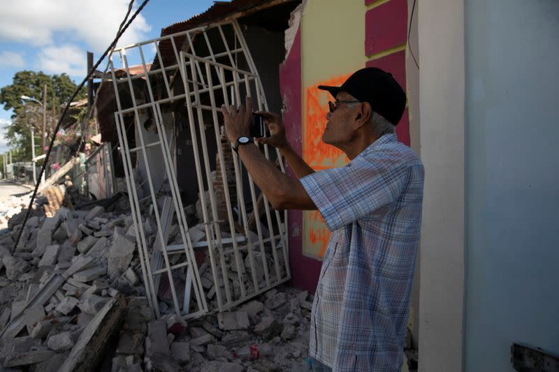 A man uses his phone to take photos of damaged houses after an earthquake in Guanica