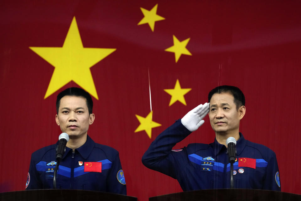 Chinese astronauts Nie Haisheng, right, salutes as he and fellow astronaut Tang Hongbo attend a press conference at the Jiuquan Satellite Launch Center ahead of the Shenzhou-12 launch from Jiuquan in northwestern China, Wednesday, June 16, 2021. China plans on Thursday to launch three astronauts onboard the Shenzhou-12 spaceship, who will be the first crew members to live on China's new orbiting space station Tianhe, or Heavenly Harmony from the Jiuquan Satellite Launch Center in northwest China. (AP Photo/Ng Han Guan)