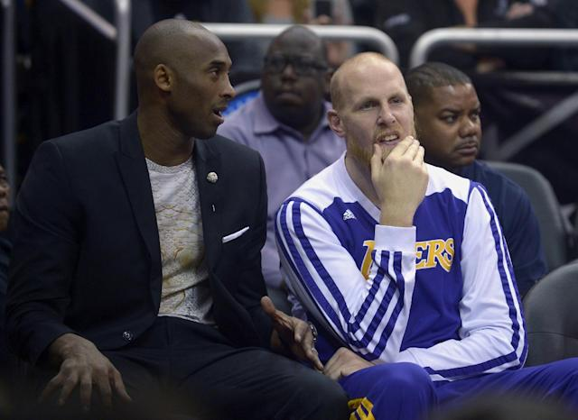 Los Angeles Lakers guard Kobe Bryant, left, talks to center Chris Kaman on the end of the bench during the first half of an NBA basketball game against the Orlando Magic in Orlando, Fla., Friday, Jan. 24, 2014. (AP Photo/Phelan M. Ebenhack)