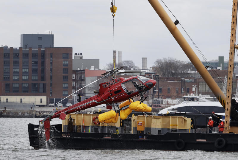 FILE - In this March 12, 2018 file photo, a helicopter is hoisted by crane from the East River onto a barge in New York. Federal investigators said Tuesday, Dec. 10, 2019, the helicopter company, whose doors-off flight crashed in a New York City river last year, exploited a regulatory loophole to avoid stricter safety requirements. (AP Photo/Mark Lennihan, File)