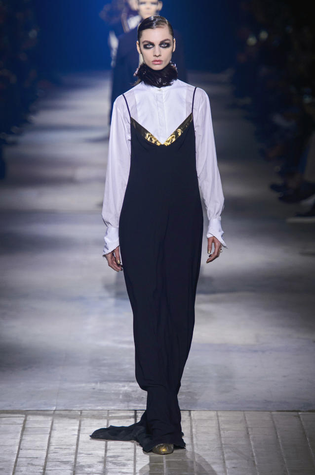 <p>A model walking in the Dries Van Noten show wore a crisp white shirt under a long, black slip dress with gold detailing along the chest. </p><p><i>(Photo: ImaxTree)</i></p>
