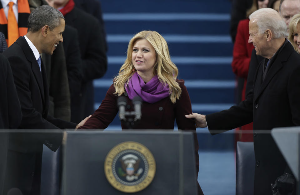 FILE - Singer Kelly Clarkson is greeted by President Barack Obama, left, and Vice President Joe Biden at the ceremonial swearing-in at the U.S. Capitol during the 57th Presidential Inauguration Jan. 21, 2013, in Washington. A-list celebrities are flocking back to inaugural events four years after many stayed away from the inauguration of Donald Trump, hugely unpopular in Hollywood. (AP Photo/Pablo Martinez Monsivais, File)