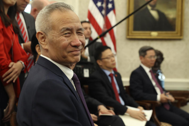 FILE - In this Oct. 11, 2019, file photo, Chinese Vice Premier Liu He listens during a meeting in the Oval Office of the White House with President Donald Trump in Washington. China's government says its Liu will go to Washington next week for the signing of an interim trade deal. (AP Photo/Andrew Harnik, File)
