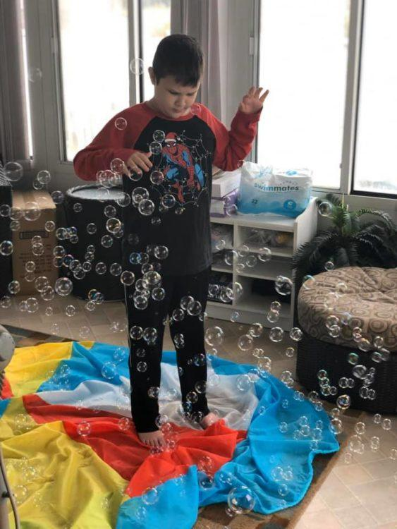 boy playing with bubbles in the house