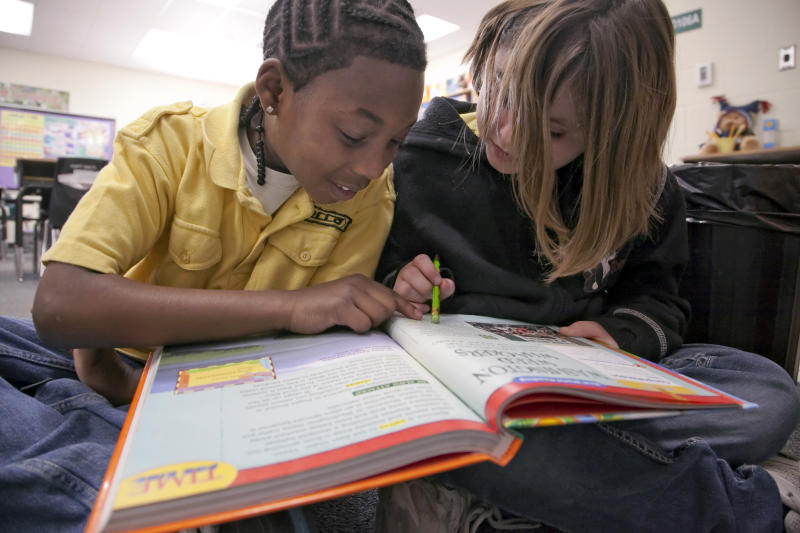 In this Jan. 23, 2013 photo Jefferson Elementary third graders Qwalynde Cain, left, and Sata Lumpkins work on a reading assignment during class in Wichita, Kan.  Kansas is one of an increasing number of states that are not promoting students who are struggling to read at the end of third grade. Thirty-two states have passed legislation designed to improve third-grade literacy, according to the Education Commission of the States. (AP Photo/Mike Hutmacher)