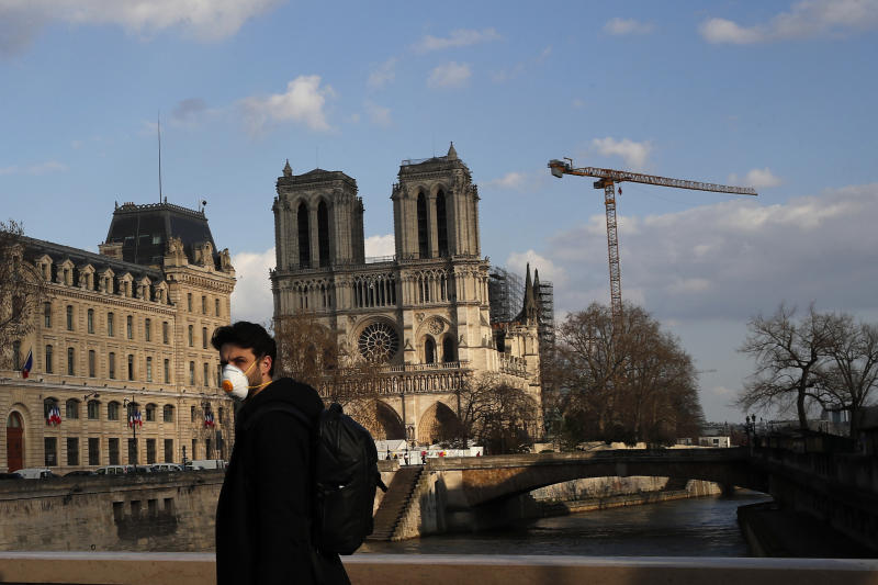 A masked man walks next to Notre Dame Cathedral, in Paris, Wednesday, March 18, 2020. French President Emmanuel Macron said that for 15 days people will be allowed to leave the place they live only for necessary activities such as shopping for food, going to work or taking a walk. For most people, the new coronavirus causes only mild or moderate symptoms. For some it can cause more severe illness, especially in older adults and people with existing health problems. (AP Photo/Francois Mori)